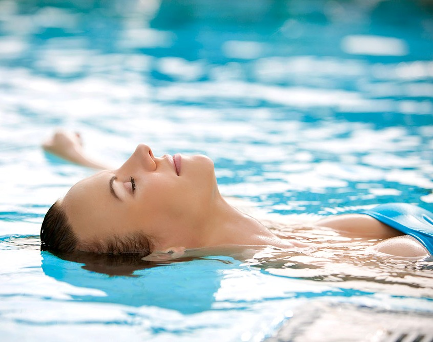 a woman is lying in the warm thermal water