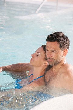 a couple relaxes together in the thermal water